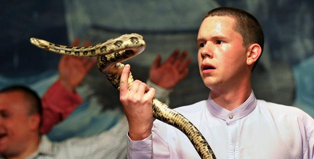 Andrew Hamblin, 21, pastor of Tabernacle Church of God in LaFollette, Tenn., looks into the eyes of a rattlesnake while worshipers sing songs April 13. Hamlin is part of a new generation of serpent handling Christians.