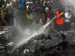 People gather at the site of a plane crash in Lagos, Nigeria.