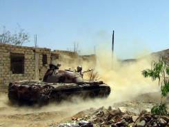 Yemeni army soldiers ride a tank as they search for militant supporters of al-Qaeda.
