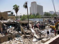 Rescuers search for victims at the site of a car explosion Monday in Baghdad.