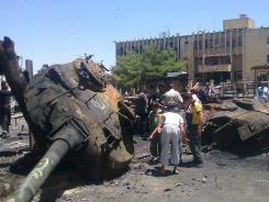 Anti-Syrian regime citizens look at a Syrian tank that was damaged during clashes between rebels and government forces.