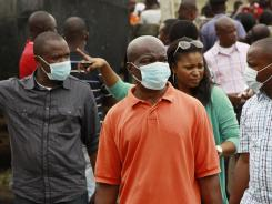 Family members who lost their loved ones in a plane crash wait to identify their bodies in Lagos, Nigeria, on Tuesday.