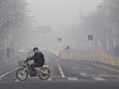 A man rides an electric bike crossing a street shrouded by haze in Beijing in January.
