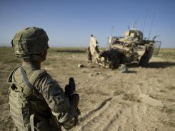 Spc Jason Aguilar looks at his Mine Resistant Ambush Protected vehicle, after it was blown up by an IED near the village of Nasow Khevl, Afghanistan, on Sept. 9.