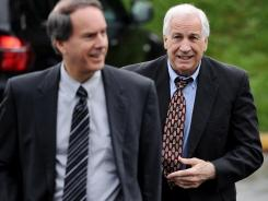 Former Penn State assistant football coach Jerry Sandusky, right, and his lawyer, Joe Amendola, walk into a courthouse Tuesday.