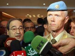 Syria's Deputy Foreign Minister Faisal al-Miqdad, left, speaks to the press following a meeting with U.N. mission chief in Syria Major General Robert Mood, right, in Damascus.