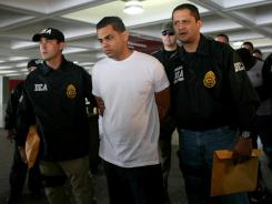 Drug Enforcement Administration officers escort a suspect after his arrest on drug smuggling charges in San Juan, Puerto Rico.