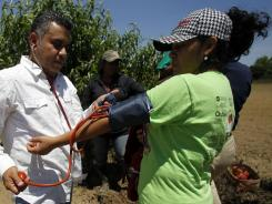 Rafael Carcache takes the blood pressure of Josephina Sanches in the field in Slocomb, Ala.