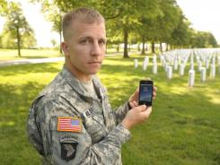 Army Maj. Nick Miller, chief information officer for Arlington National Cemetery, holds an iPhone with the mobile app that will permit visitors to locate a loved one's grave.