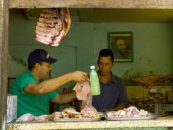 A butcher works in his shop in Havana. Some Cubans are allowed to run private restaurants in their homes.