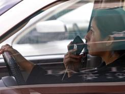 A driver uses a cellphone in Los Angeles in 2011. The push is on for a ban on mobile devices by drivers.