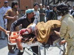 A Pakistani man, who was injured in a bomb blast, is wheeled on a stretcher to a hospital, in Peshawar.