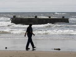 A woman looks at the massive dock that washed ashore on Agate Beach Wednesday in Newport, Ore.