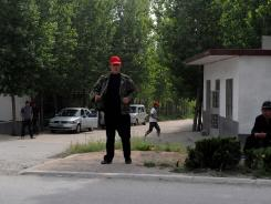 Plainclothes security monitor the entrance to Dongshigu village on April 28. The village was once home to blind activist Chen Guangcheng.