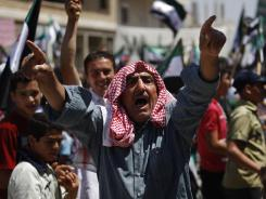 A Syrian man chants slogans during an anti-Bashar Assad protest after Friday prayers on the outskirts of Idlib, Syria.