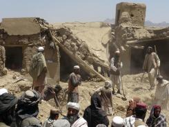 Afghan villagers gather near a house destroyed in an apparent NATO raid in Logar province.