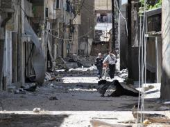 Syrians walk in a destroyed alley damaged from shelling of army forces.