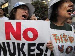 Protesters shout slogans during an anti-nuclear plant rally in front of the prime minister's office in Tokyo on Friday.