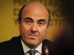 Spanish Economy Minister Luis de Guindos listens during a news conference in Madrid on Saturday.