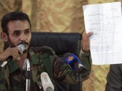 Ajmi al-Atiri, commander of the Zintan brigade that arrested Seif al-Islam, the detained son of slain leader Moammar Gadhafi, shows a document during a press conference.
