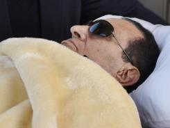 Former Egyptian president Hosni Mubarak is wheeled into court in Cairo on Jan. 29.