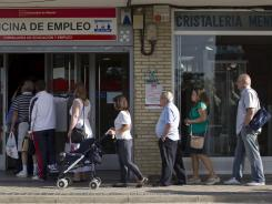 People enter an unemployment registry office in Madrid. Prime Minister Mariano Rajoy said Sunday that the economic misery will continue and more Spaniards will lose their jobs.