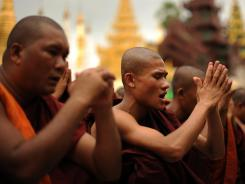 Rakhine Buddhist monks pray as hundreds of demonstrators gather at the Shwedagon pagoda after unrest flared.