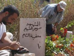 A handout image released by the Syrian opposition's Shaam News Network shows a man painting the gravestone of a victim who was allegedly killed during violence in Qusayr.