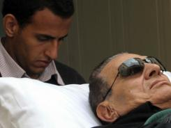 Hosni Mubarak is wheeled on a stretcher into court for his trial in Cairo on Jan. 5.