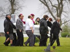 Pallbearers with pink and orange accents in their hair carry the casket of Kenneth Weishuhn, a freshman at South O'Brien High School who hanged himself.