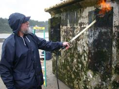 A worker near Newport, Ore., burns debris from a dock float torn loose from a Japanese fishing port by the 2011 tsunami.