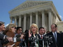 Arizona Gov. Jan Brewer speaks at the U.S. Supreme Court in Washington on April 25 after arguments on the state's immigration law.