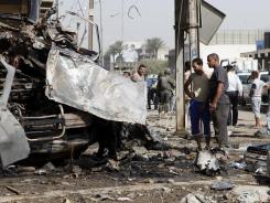 Security forces and residents inspect the scene of a car bombing Wednesday in Baghdad's Karrada neighborhood.
