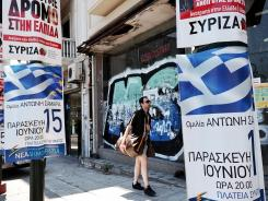 A man passes by election posters of the conservative New Democracy Party and the Syriza coalition in central Athens.