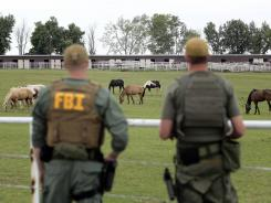 FBI agents inspect the horse ranch raided Tuesday in Lexington, Okla.