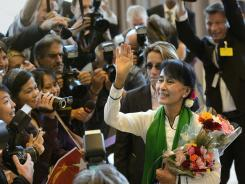 Burma's Aung San Suu Kyi waves as she arrives at the United Nations in Geneva on Thursday.