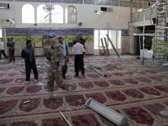 U.N. observers inspect the prayer hall of the Sayyida Zainab shrine in Damascus, which was damaged after a car bomb exploded near the site.