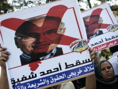 "Protesters carry posters with defaced pictures of presidential candidate Ahmed Shafiq Thursday in front of the Supreme Constitutional Court in Cairo. The Arabic reads ""down with Ahmed Shafiq."""