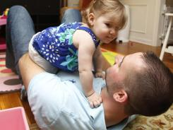 Calmer, quieter: Keith Liadis, 29, plays with his 1-year-old daughter, Ella, at their home in Bedford, N.H. Liadis says being a dad makes him think twice about taking risks.