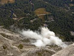A dust cloud is seen from the Glacier Point overlook during a rock fall that damaged lodging facilities at Curry Village in Yosemite National Park, Calif., on Oct. 8, 2008.