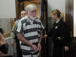 Carl V. Ericsson, 73, is escorted into Lake County Court on Feb. 1 in Madison, S.D., to face first degree murder charges in the slaying of Norman Johnson.