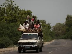 Residents of Yemen sit on a vehicle driving along a road leading to the town of Jaar in the southern Abyan province.