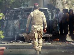 Iraqi security forces and civilians inspect the scene of a car bomb attack in the Kazimiyah area of Baghdad, Iraq.