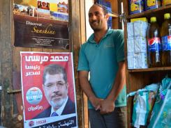 Mohammad Bedouina stands next to a poster of presidential hopeful Mohammed Morsi at his shop in Dahab, a town on the Red Sea coast.
