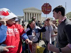 Several women argue with a supporter of President Obama's health care law in March in front of the Supreme Court.