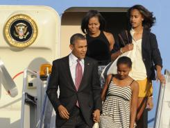 President Obama and first lady Michelle Obama, along with daughters Sasha, front right, and Malia back right, walk off Air Force One after arriving at O'Hare International Airport in Chicago on Friday.
