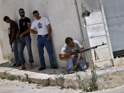 A Free Syrian Army fighter fires his weapon during clashes with Syrian troops near Idlib, Syria, on Friday.