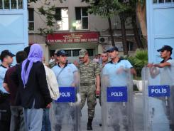 Relatives of prisoners wait as Turkish policemen and soldiers stand guard in front of Sanliurfa city prison on Sunday.
