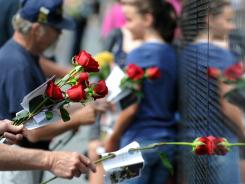 People lay roses on the wall at the Vietnam Veterans Memorial. Red roses are for those killed in combat, yellow for those missing in action and white for those who have recently died.