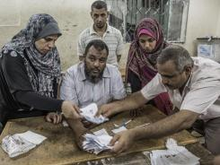 Egyptian election workers count votes at a polling station Sunday in Cairo.